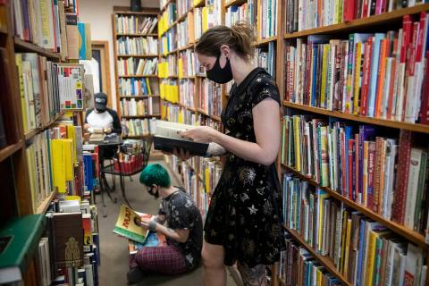 Friends Mercury Taft, left, and Stephanie Lehr, right, shop for books at Amber Unicorn Books in ...