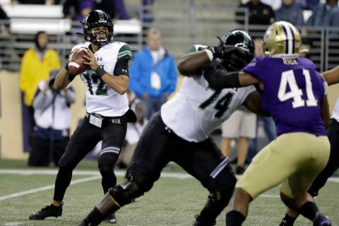 Hawaii backup quarterback Chevan Cordeiro, left, throws against Washington during the second ha ...