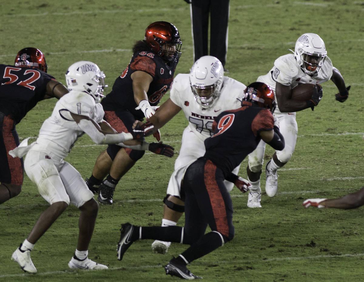 UNLV's Charles Williams tries to run the ball through the San Diego State defense during Satu ...