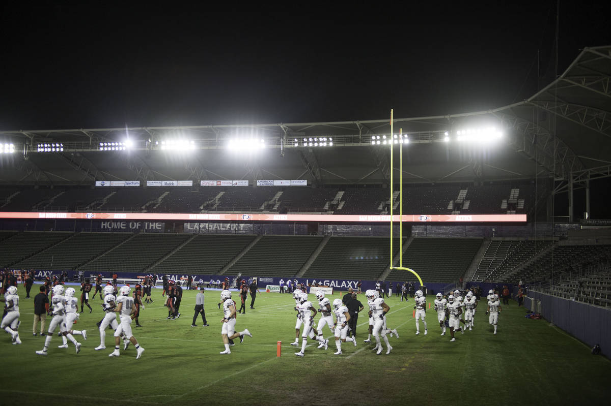 The UNLV Rebels take the field to warm up under the light of a near empty stadium before the st ...