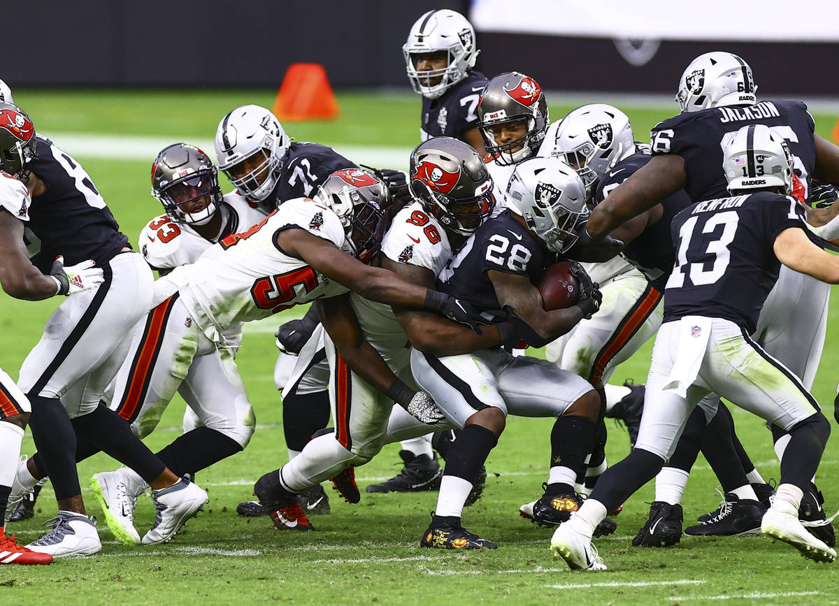 Las Vegas Raiders running back Josh Jacobs (28) gets stopped by Tampa Bay Buccaneers defensive ...