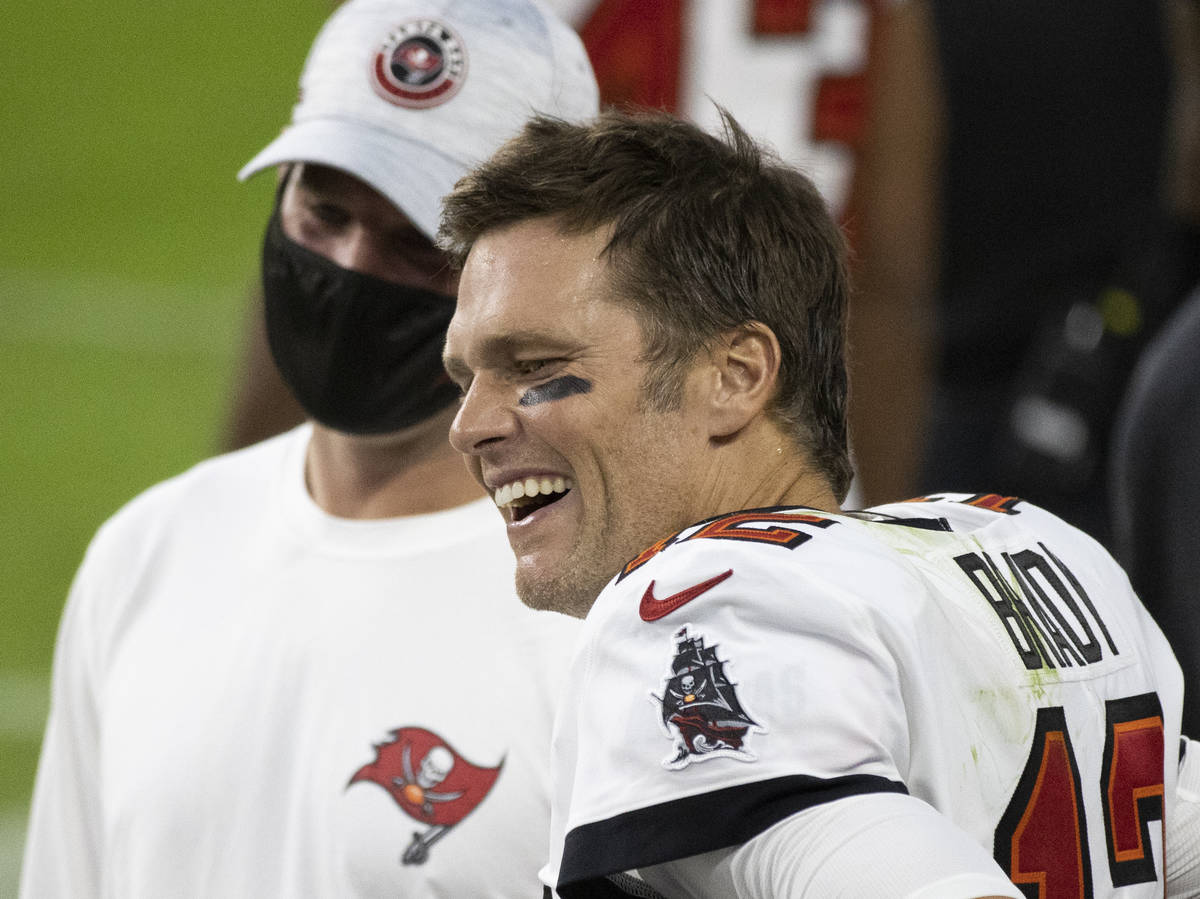 Tampa Bay Buccaneers quarterback Tom Brady (12) shares a laugh with teammates in the fourth qua ...