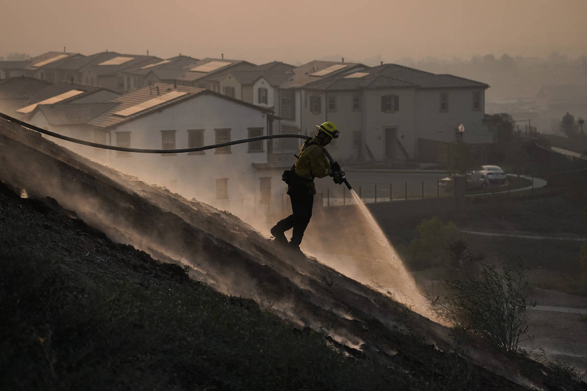 Firefighter Tylor Gilbert puts out hotspots while battling the Silverado Fire, Monday, Oct. 26, ...