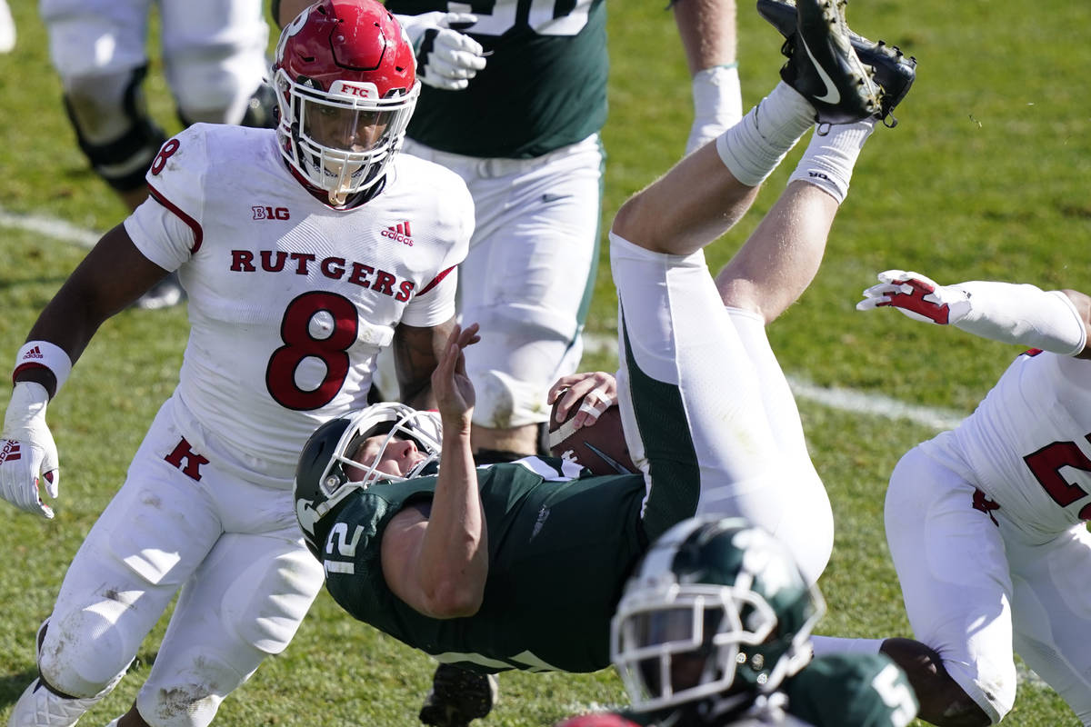Michigan State quarterback Rocky Lombardi (12) jumps over Rutgers defensive back Lawrence Steve ...