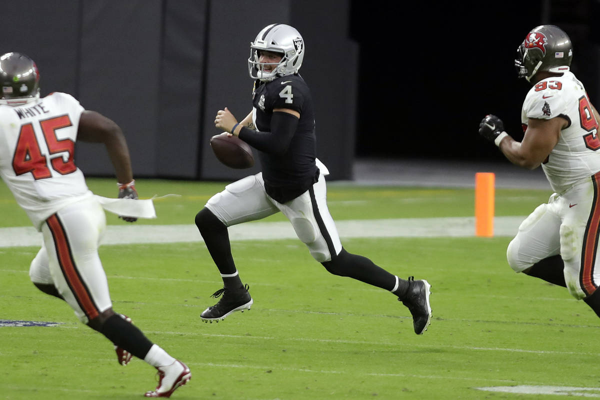Raiders quarterback Derek Carr carries the ball during the second half of an NFL football game, ...