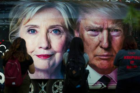 People take photos of a bus depicting Democratic presidential candidate Hillary Clinton and Rep ...