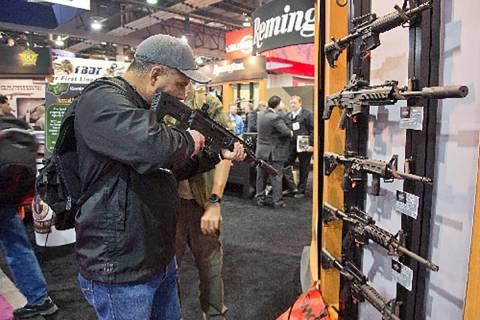 Stuart Konicar of Scottsdale, Ariz., looks down the sight of a Remington Adaptive Combat Rifle ...