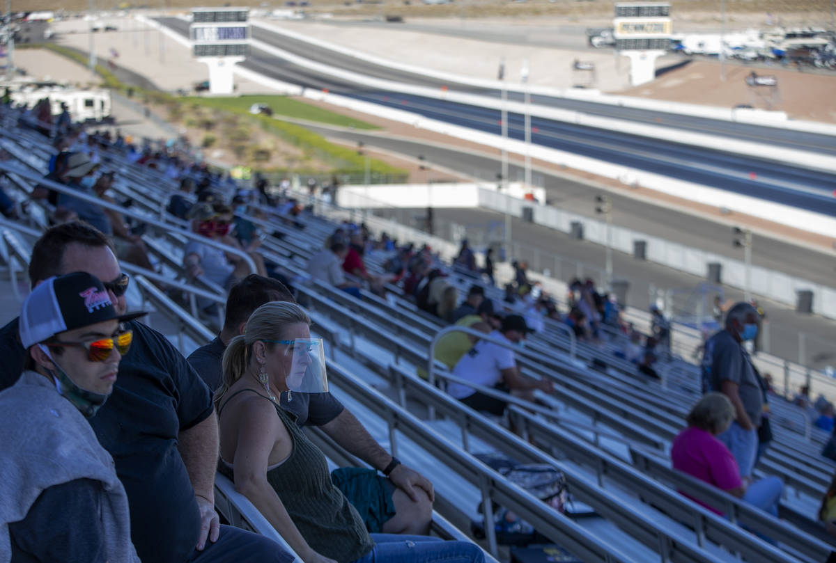 Some fans wear personal protective equipment while watching the Dodge NHRA Finals at Las Vegas ...