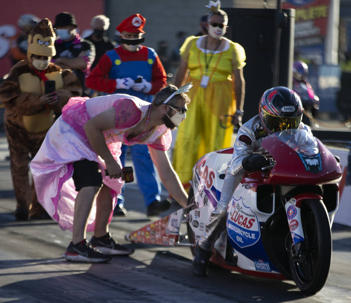 Crew members wear Halloween costumes as Pro Stock driver David Barron gets ready to race during ...