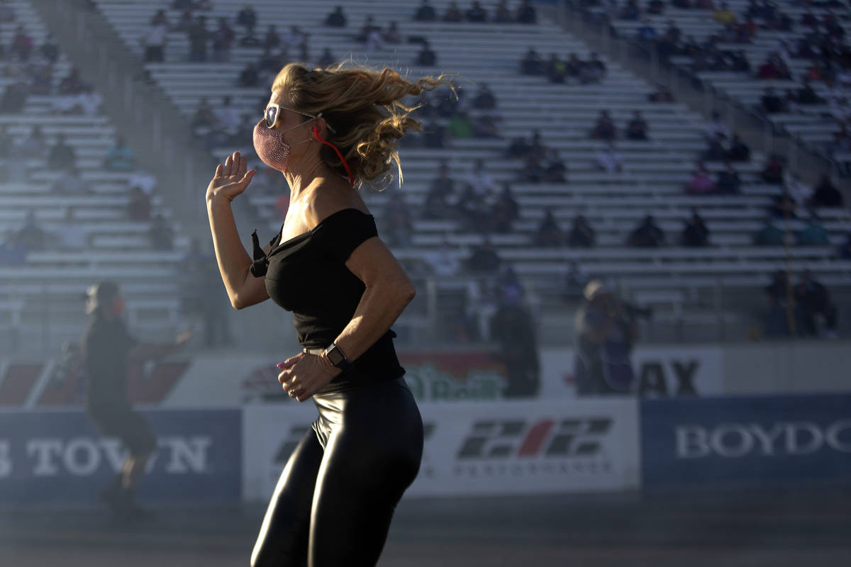 A member of Funny Car driver Alex Miladinovich's crew runs on the track during the Dodge NHRA F ...