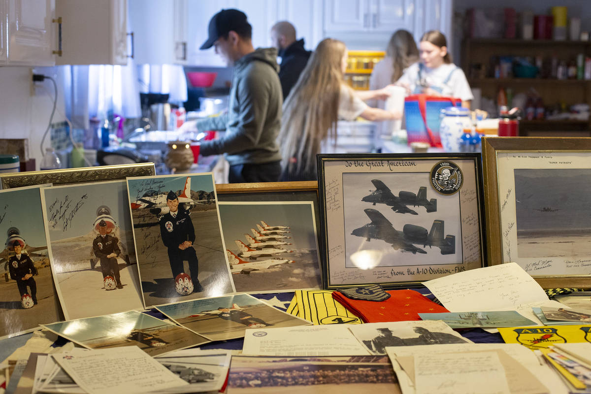 Photos and trinkets honor Navy veteran Evan Thompson III as his family and friends gather for a ...