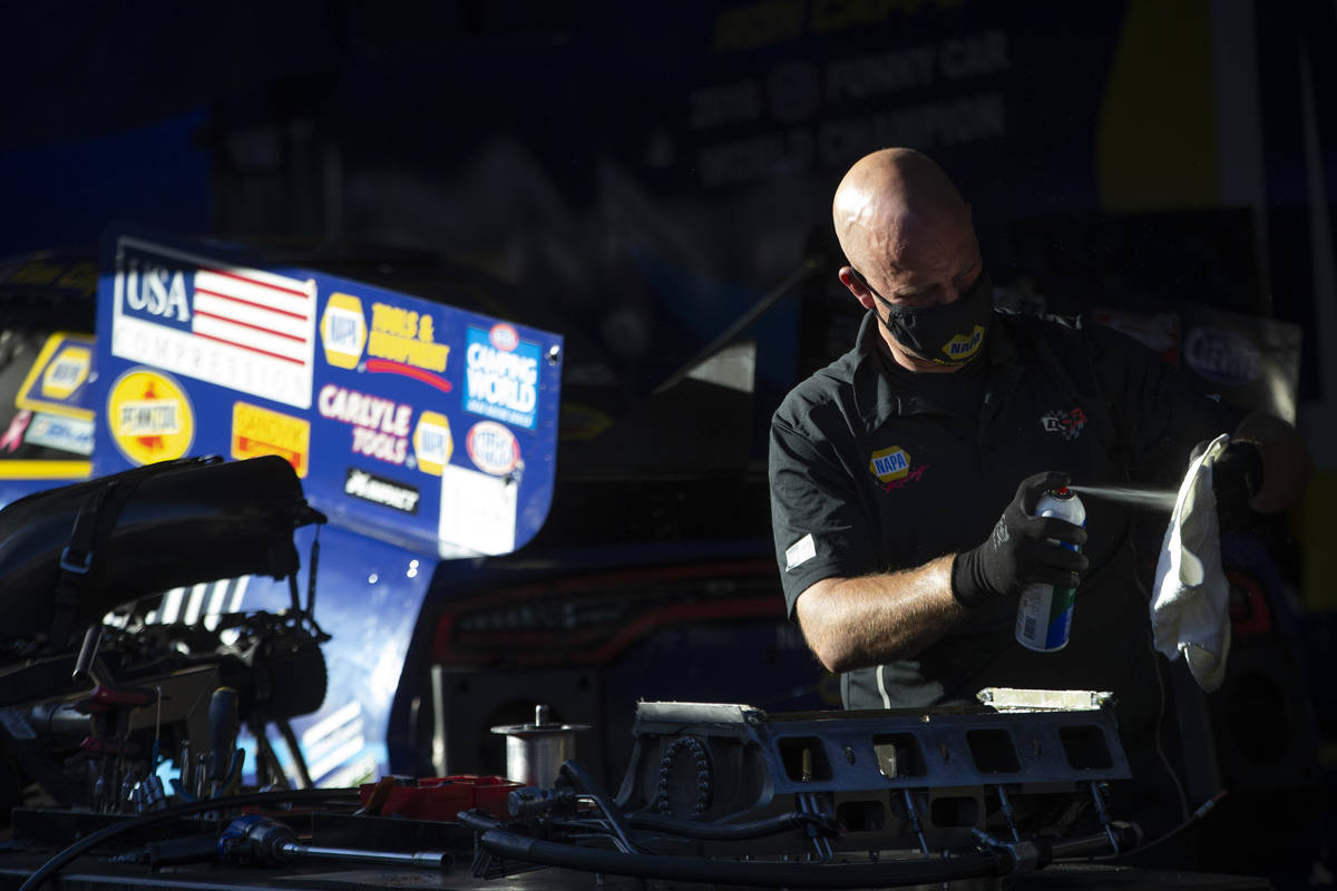 A member of Funny Car driver Ron Capps' crew services the team's car during the Dodge NHRA Fina ...