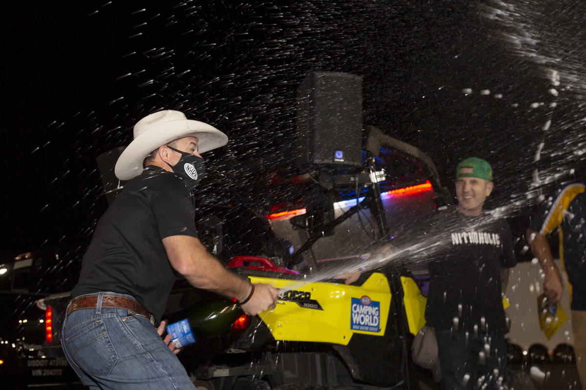 Top Fuel driver Steve Torrence sprays champagne in celebration of winning the NHRA Camping Worl ...
