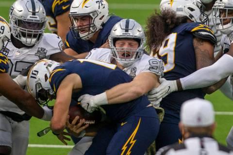 Las Vegas Raiders defensive end Maxx Crosby (98) sacks Los Angeles Chargers quarterback Justin ...
