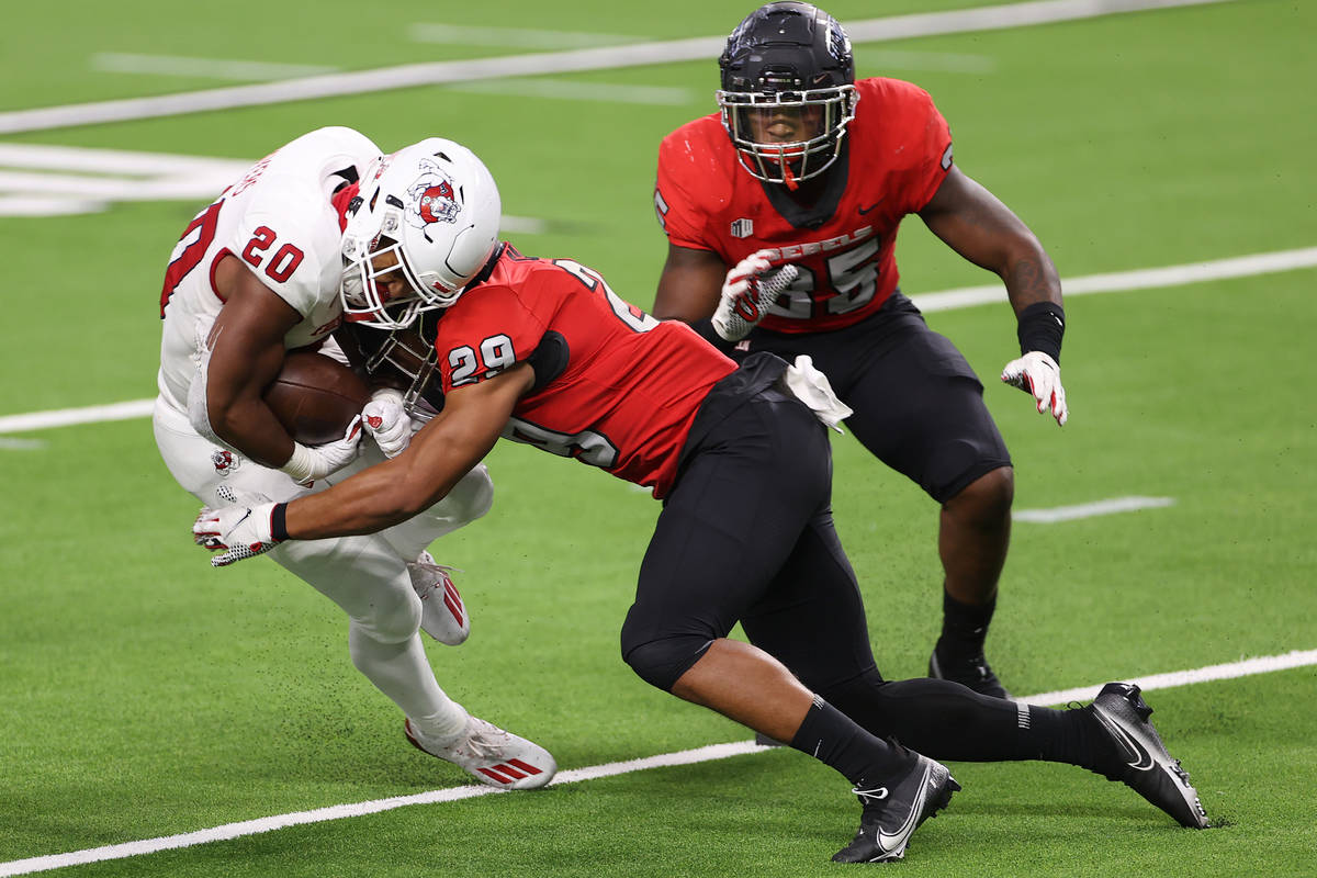 Fresno State Bulldogs running back Ronnie Rivers (20) is tackled by UNLV Rebels defensive back ...