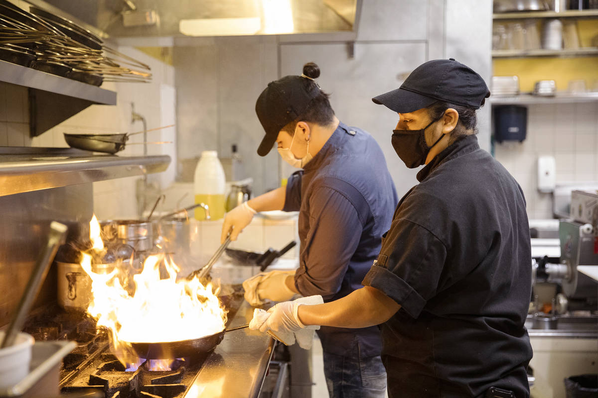 Chef Omar Velazquez, left, and Chef Denise Ortiz, right, cook in the kitchen at Pasta Shop Rist ...