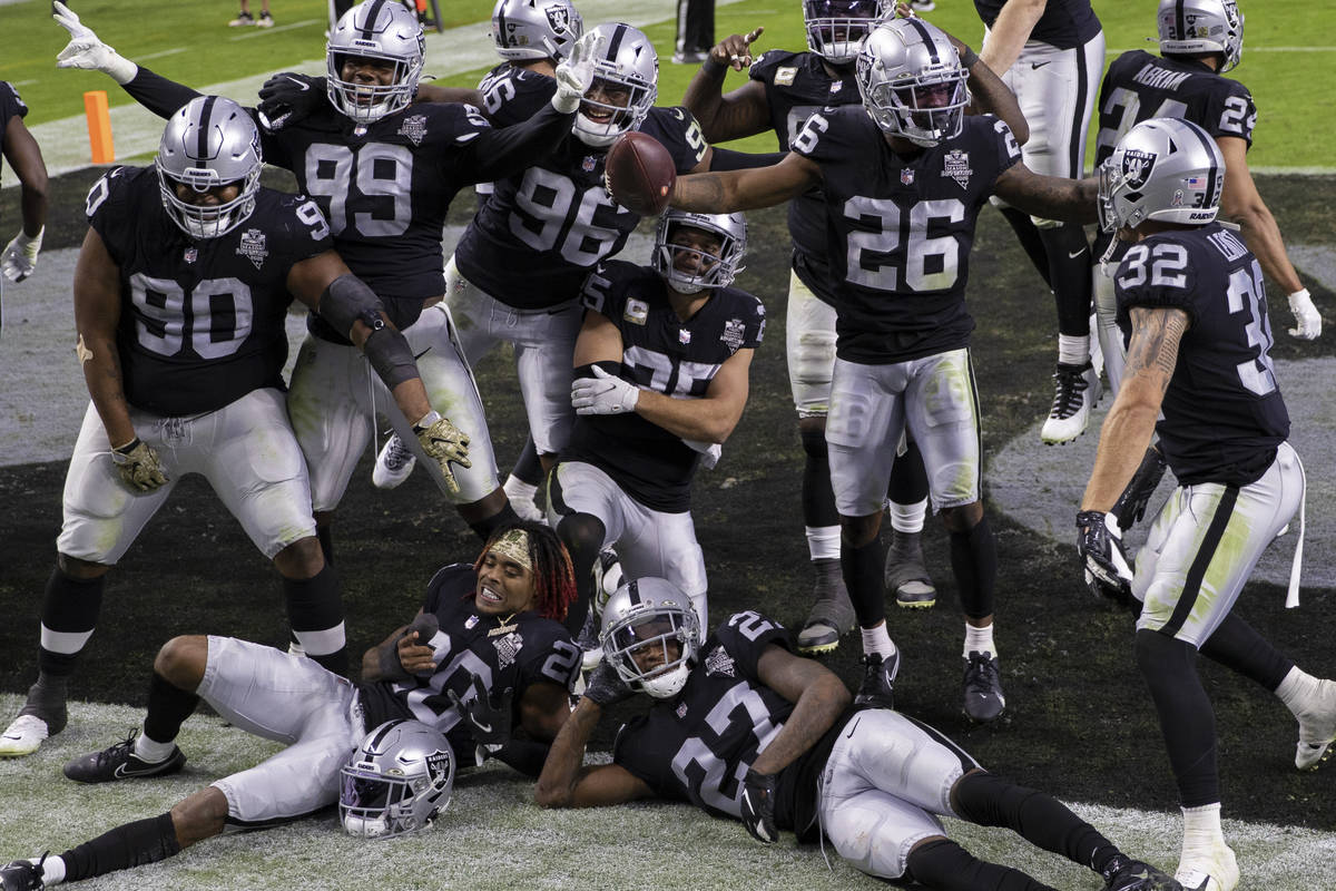Las Vegas Raiders defensive players celebrate after recovering a fumble in the fourth quarter d ...