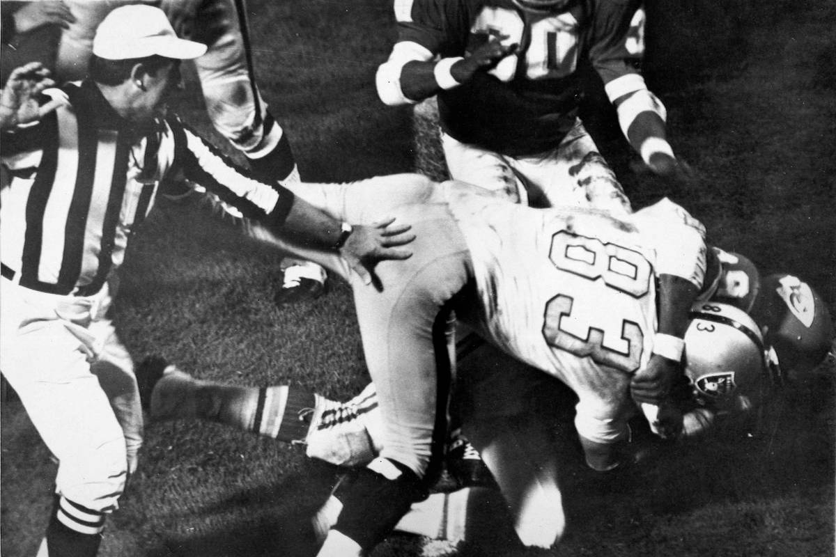 Otis Taylor of the Kansas City Chiefs, underneath, grabs Ben Davidson, on top, of the Oakland R ...