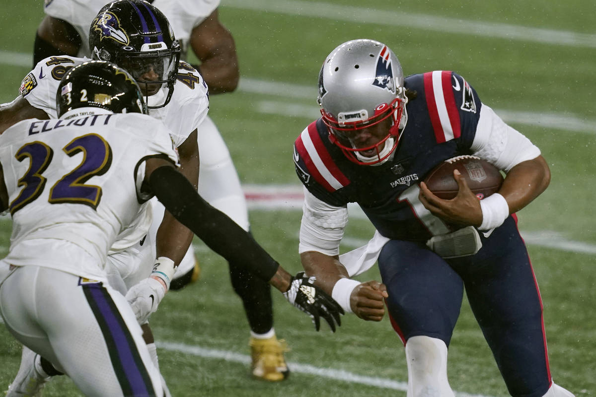 New England Patriots quarterback Cam Newton (1) carries the ball as Baltimore Ravens safety DeS ...