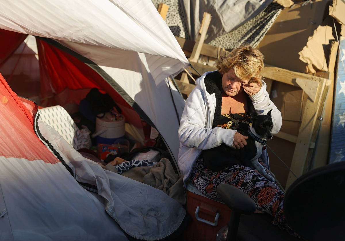 Faythe Simpson Zhang sits outside her tent after checking in with Help of Southern Nevada and t ...