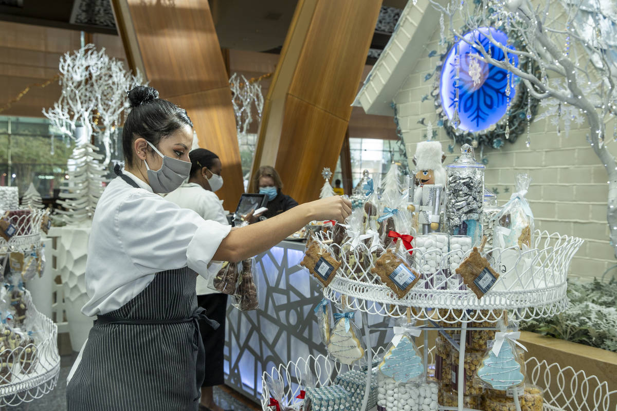 Aria's assistant pastry chef Andrea Madrid arranges treats in the retail area during the unveil ...
