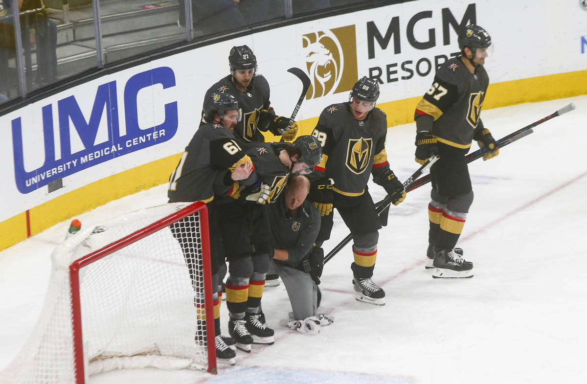 Golden Knights' Cody Glass (9) is escorted off the ice with the help of teammates during the th ...