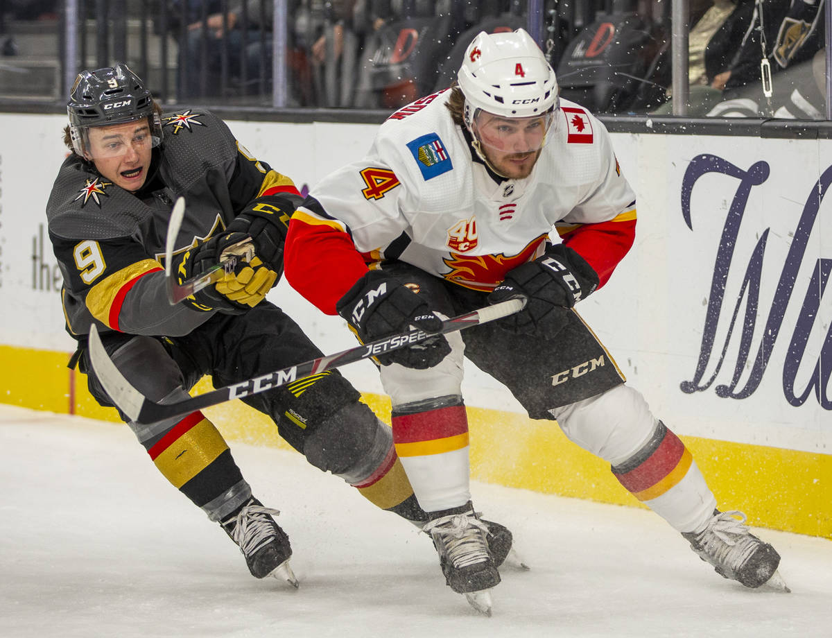 Vegas Golden Knights center Cody Glass (9, left) battles on the ice with Calgary Flames defense ...