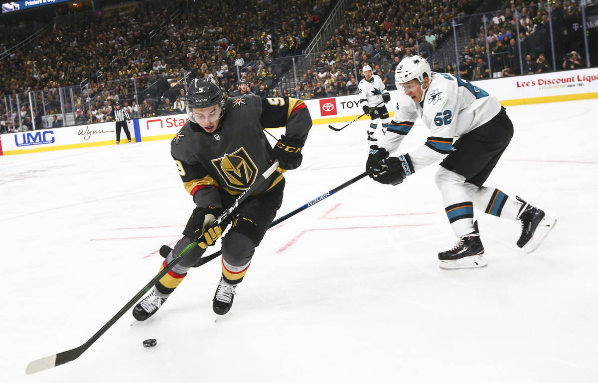 Golden Knights' Cody Glass (9) skates with the puck around San Jose Sharks' Lukas Radil (52) du ...