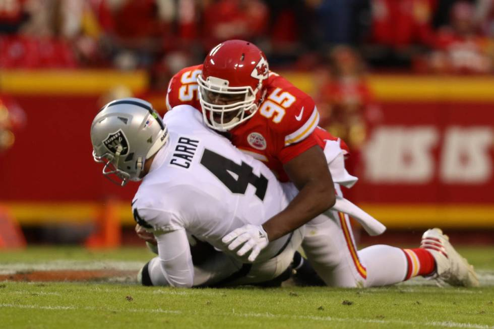Oakland Raiders quarterback Derek Carr (4) is sacked by Kansas City Chiefs defensive end Chris ...