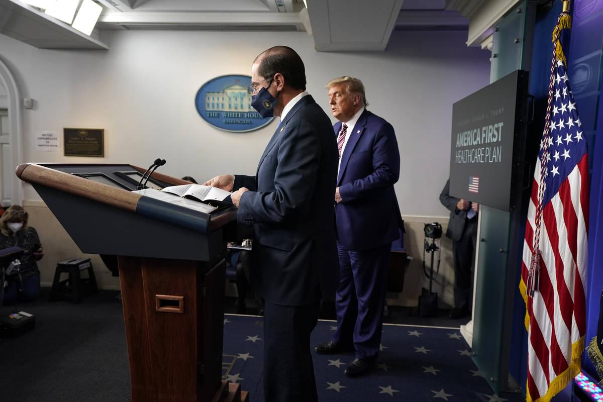 President Donald Trump listens as Health and Human Services Secretary Alex Azar prepares to spe ...