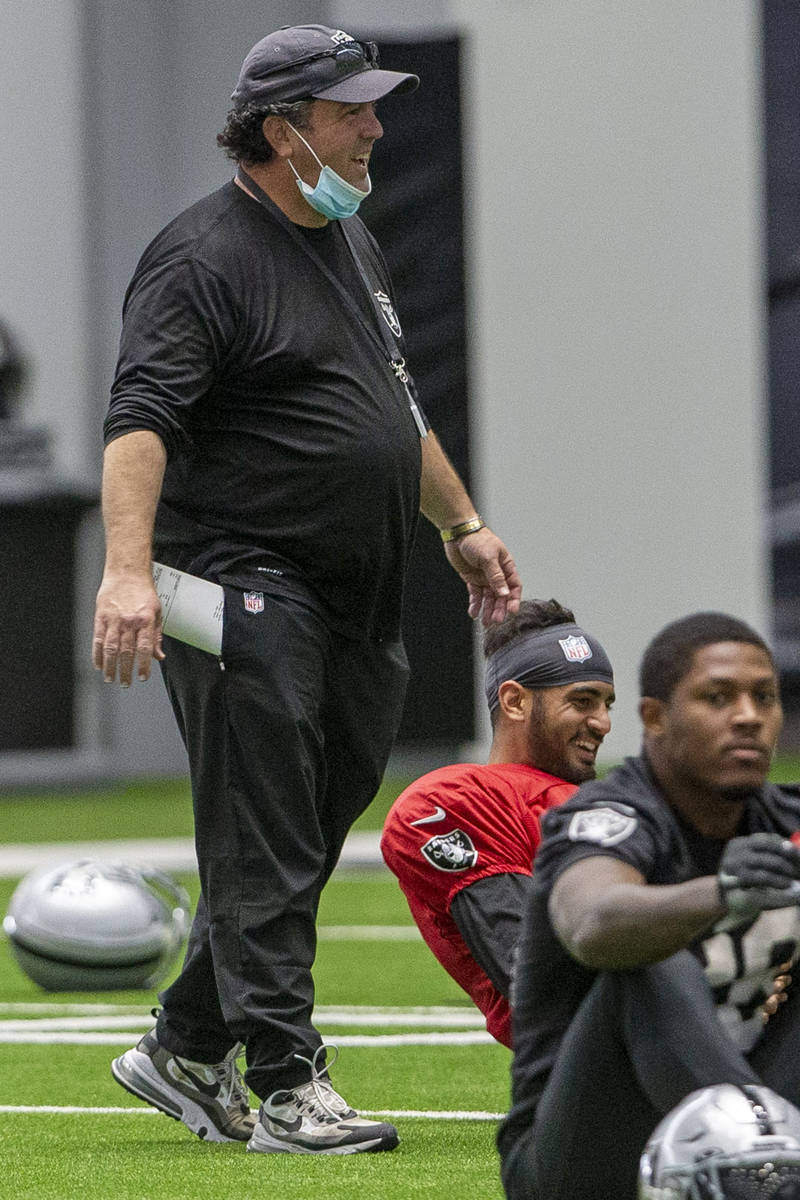Las Vegas Raiders defensive coordinator Paul Guenther, left, gets laughs from quarterback Marcu ...