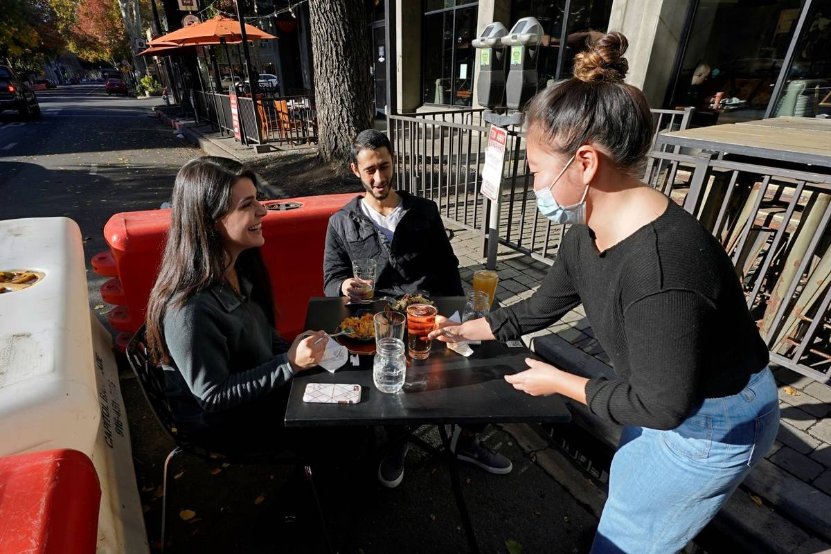 Server Tami Bat, right, brings drinks to Ranim Abaad, left, and Joey Bettencourt, right, having ...