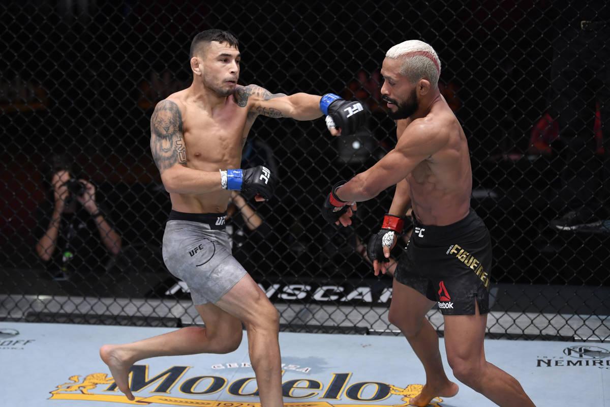 LAS VEGAS, NEVADA - NOVEMBER 21: (L-R) Alex Perez punches Deiveson Figueiredo of Brazil in the ...