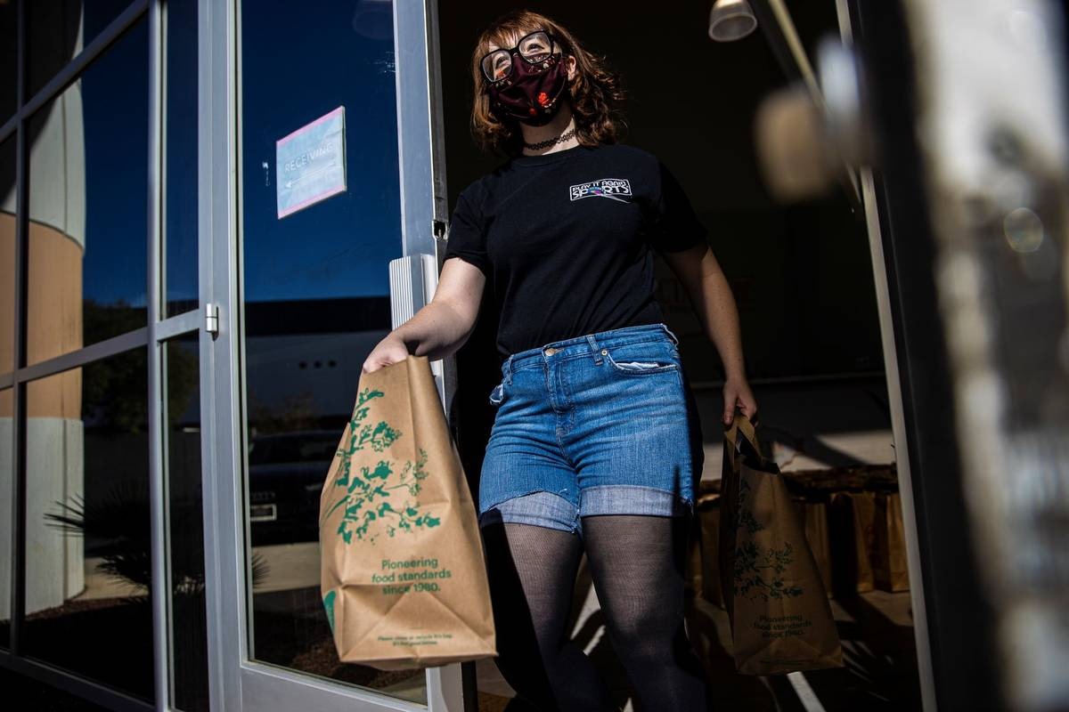 Human resources worker Rachel Clark delivers bags of donated food to vehicles during a food dri ...