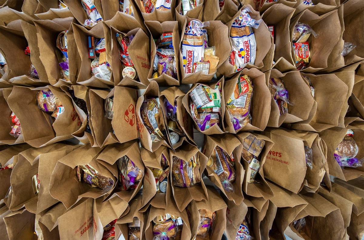 Bags of donated food wait to be handed out during a food drive hosted by Nectar Bath Treats on ...