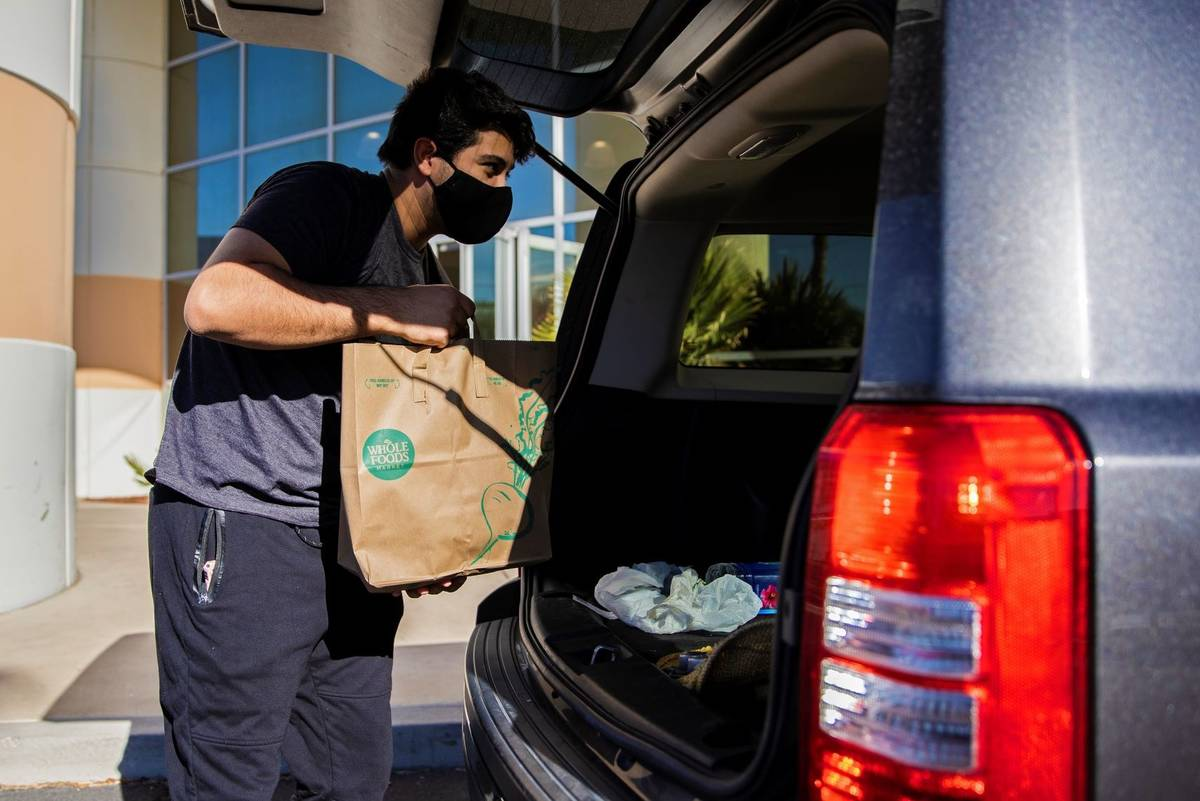 Logistics worker Tristan Sanchez delivers bags of donated food to a vehicle during a food drive ...