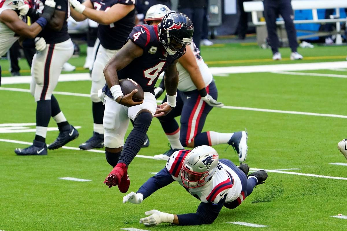 Houston Texans quarterback Deshaun Watson (4) leaps from the grasp of New England Patriots defe ...