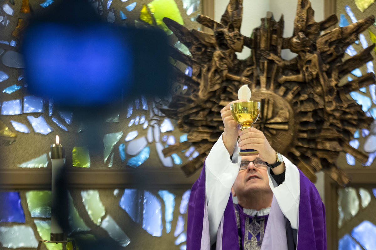 A camera records Msgr. Gregory Gordon taking Communion during a virtual Mass at the The Roman C ...