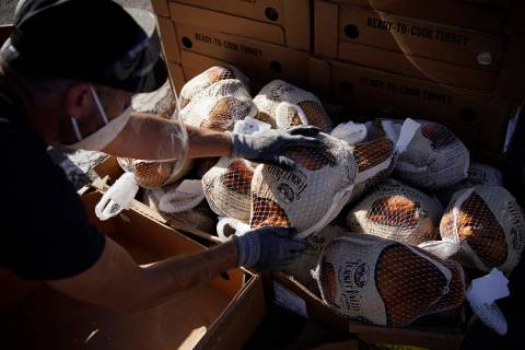 A volunteer unpacks frozen turkeys to give away at a free Thanksgiving food distribution event ...