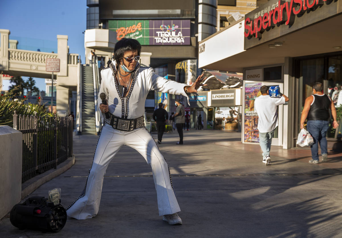 An Elvis impersonator drums up a little street business along the Las Vegas Strip on Tuesday, N ...