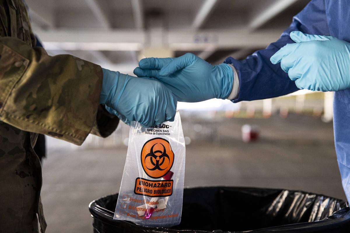 Nevada National Guard specialists Jonathan Macias, left, and Demetrie Barnett store a test tube ...
