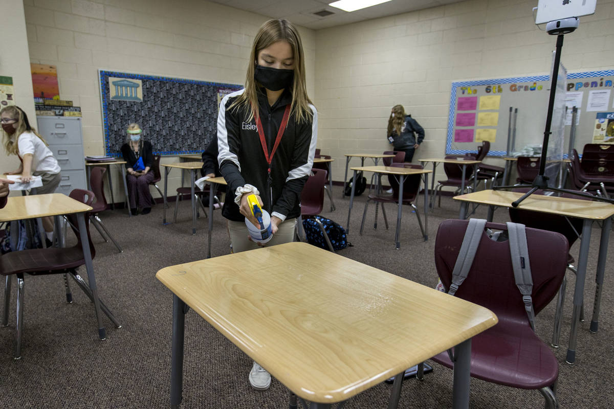 In this Sept. 24, 2020, file photo, Eisley Wheat, 12, center, sprays down a desk in her 6th gr ...
