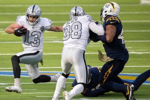 Las Vegas Raiders wide receiver Hunter Renfrow (13) turns the corner around Los Angeles Charger ...