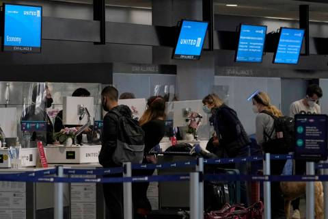 Travelers wearing masks check in at United desks at San Francisco International Airport during ...