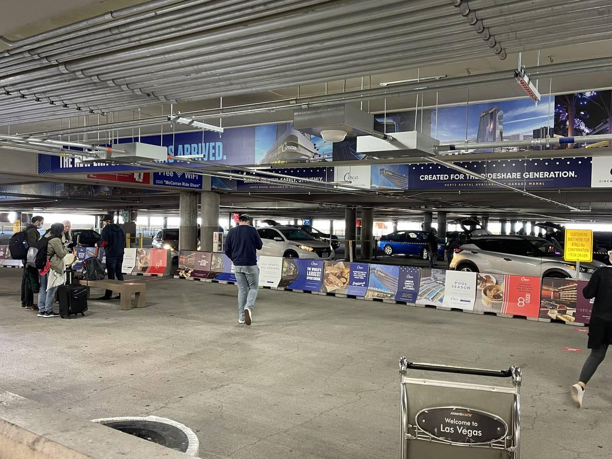 Travelers at McCarran International Airport wait for rides at the ride hailing pickup location ...