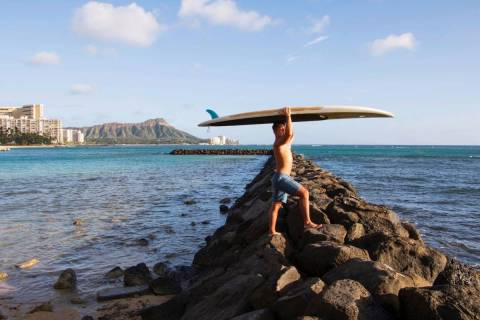 Bryant de Venecia poses for a photo with his paddleboard in Honolulu, Wednesday, Nov. 11, 2020. ...