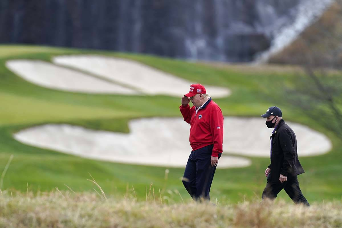 President Donald Trump salutes as he walks to board Marine One after playing golf at Trump Nati ...