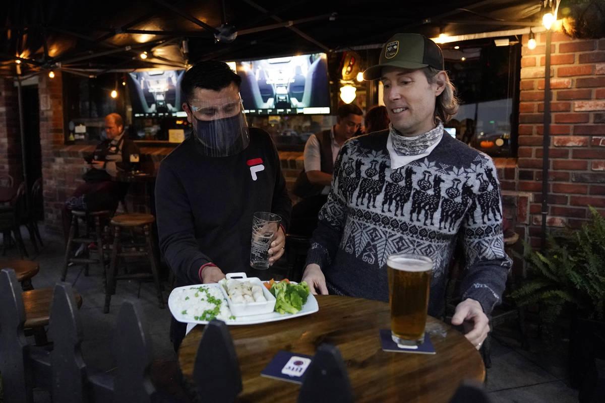 A waiter serves food to a customer at Ye Olde King's Head on Thursday, Nov. 19, 2020, in Santa ...