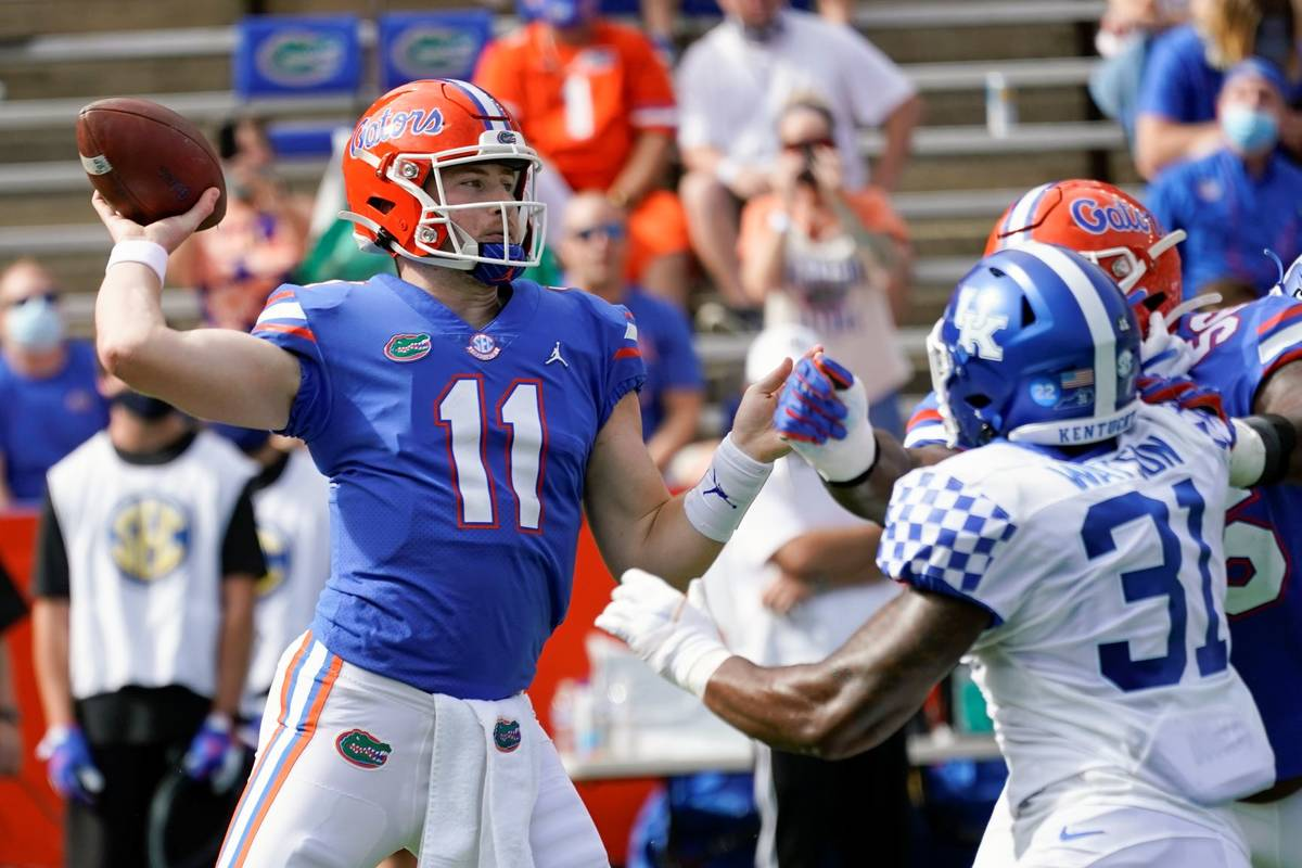 Florida quarterback Kyle Trask (11) throws a pass as Kentucky linebacker Jamar Watson (31) rush ...