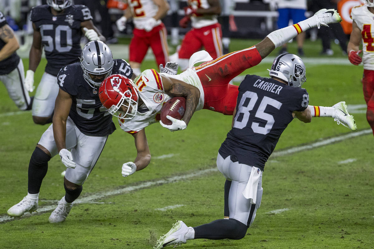 Kansas City Chiefs wide receiver Demarcus Robinson (11, center) is upended by Las Vegas Raiders ...
